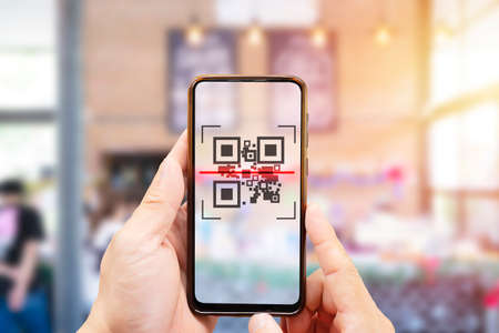 Modified inactive QR Code used. Person scanning QR code with smartphone to register details before enter outlet to comply with contact tracing rule to manage covid-19 spread. Stock Photo