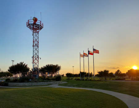 A sunset view of control tower transmission and american and texas flags in DFW Founders' Plaza in Texas