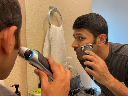Close up view of a man looking at the mirror and using the electric shaver for shaving
