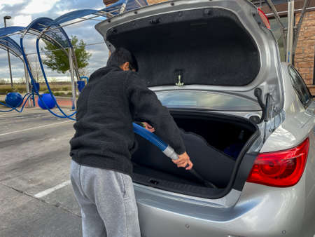 Close up view of a man using the vacuum hose to vacuum his car in the self serve vacuum parking lot