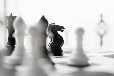 Etwas weißes und schwarzes Schach an Bord. Schachfiguren. Kooperations- und Wettbewerbskonzept- Image