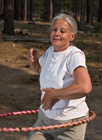 senior active woman hoola hooping. Stock Photo