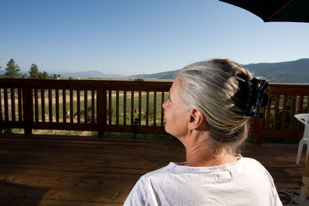 senior woman sitting on deck Stock Photo