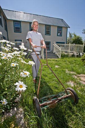 senior woman mowing lawn