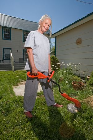 senior woman  weed wacking