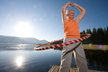 hoops: senior woman hula hooping on boat ramp