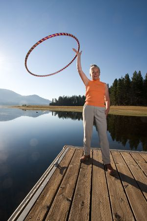 senior woman hula hooping on boat ramp