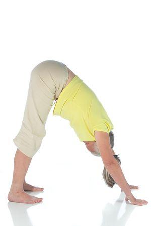 senior woman in yoga pose on white
