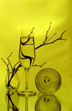 A wineglass, two glass vases and some twigs