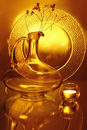 A glass jug, a candle holder with a small candle and a plate Stock Photo - 12536948
