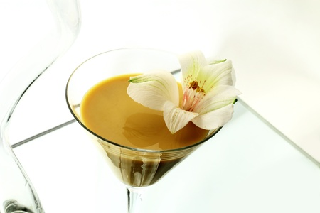 A wineglass with a liqueur and a flower