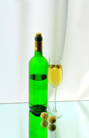 A wineglass, a bottle and two candies photo