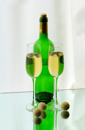 Two wineglasses, a bottle and candies on the glass photo