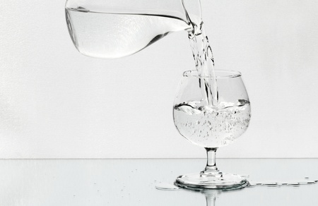Wineglass on the mirror is filled with a water from a jug