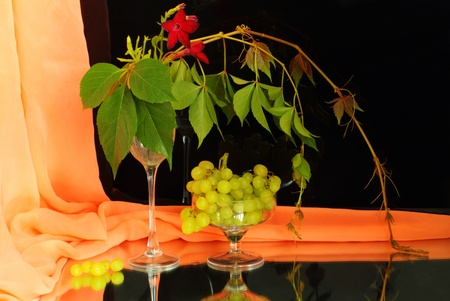 Wineglasses, grapes and a curtain on the mirror photo