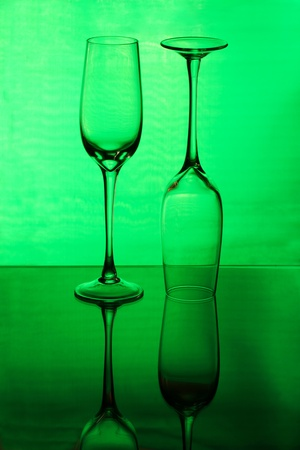 Two tall wineglasses on a green background photo