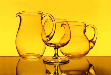 Two empty jugs and one wineglass in the yellow light photo