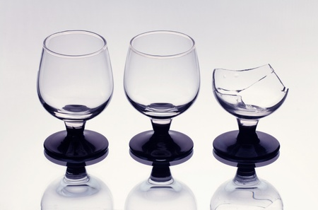 Three wineglasses including a broken one photo