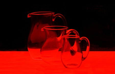 red line: Three glass jugs in the red light Stock Photo
