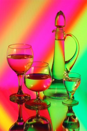 A glass jug and three wineglasses photo