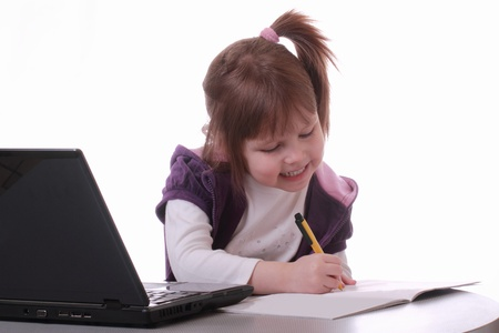 A little girl is sitting near the laptop and draws with a pen Stock Photo - 12537491