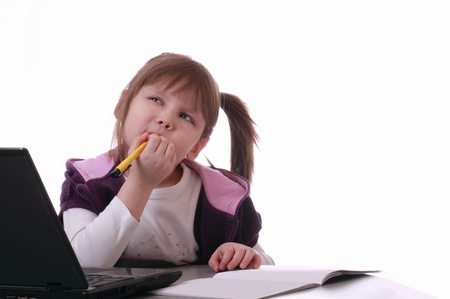 A little girl is sitting near the laptop and thinks Stock Photo - 12537405