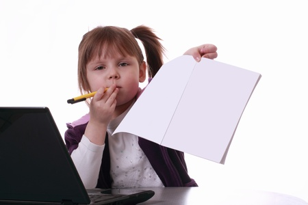 a little girl is sitting near the notebook and shows the white paper Stock Photo - 12537413