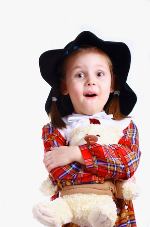 A little girl in the hat with a teddy bear