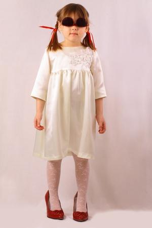 Egy kislány nagy cipő és poharak