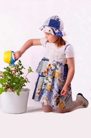A little girl waters plants photo