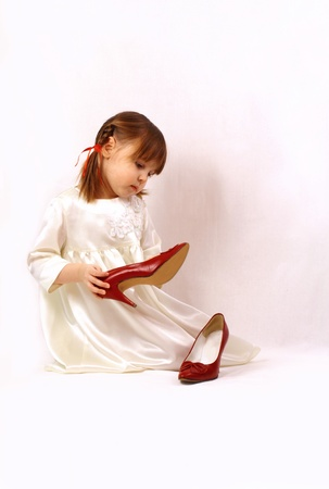 A little girl looks at the big shoes photo