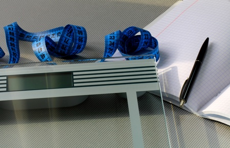 metre: Scales, metre measure ruler, pen and notebook on the table