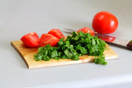 Sliced tomatoes and a parsley, a wooden board and a knife