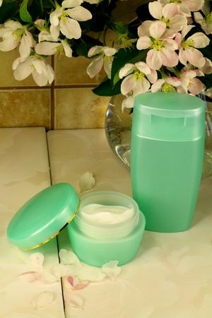 Apple tree flowers, a jar of cream and a shampoo
