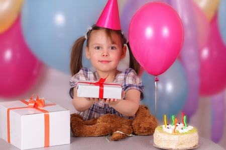 Happy little girl holds a gift on her Birthday photo