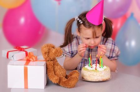 Kislány készül, hogy fújja el a gyertyákat