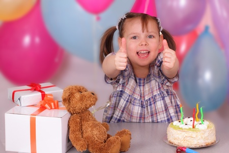 Smiling little girl with her gifts on Birthday photo