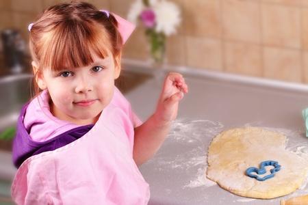 Boldog kislány főz keksz a konyhában