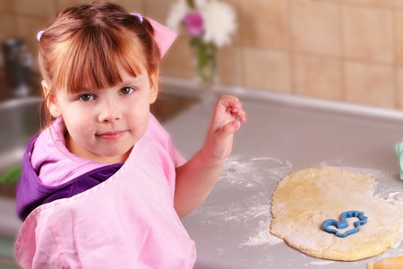 Happy little girl cooks biscuits in the kitchen Stock Photo