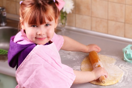 Little girl rolls the dough photo