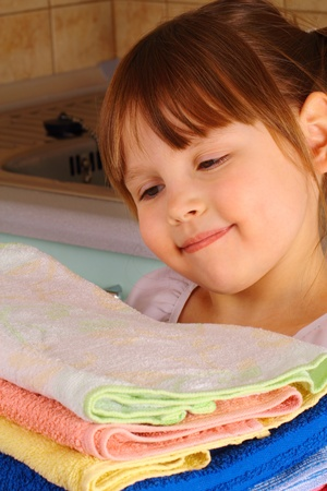 A little girl admires the towels after washing photo