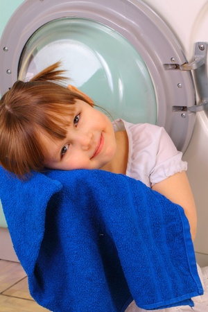 A little girl gets a towel after washing