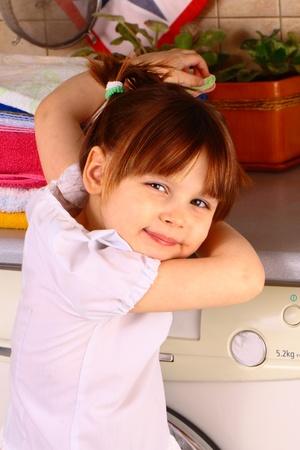 A little girl near the washing machine