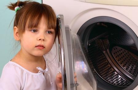 A little girl opens the washing machine Stock fotó