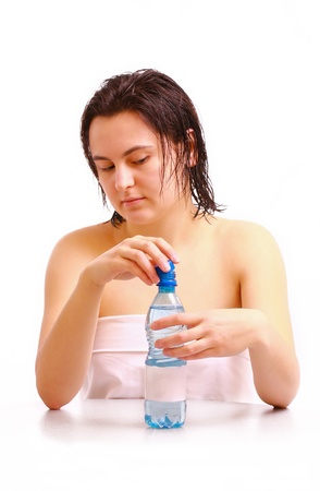 A young girl opens a bottle of mineral water Stock Photo - 12953266