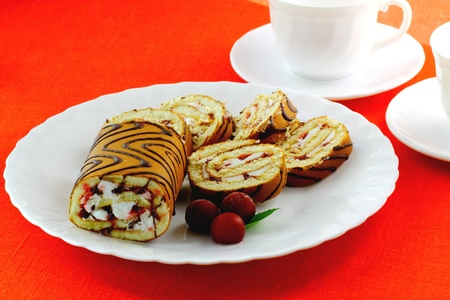 Swiss roll and three cherries on the white plate photo