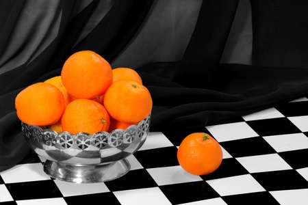 Some tangerines in the metal bowl on the chess board