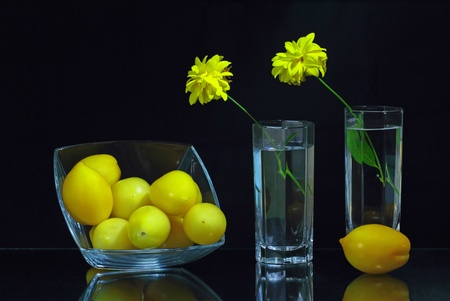 Two glasses with flowers and a glass bowl with yellow tomatoes photo