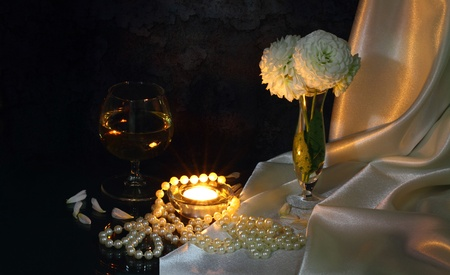 Beads, a small candle, a wineglass, a vase with white flowers, petals  and a silk cloth photo