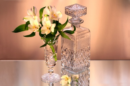 Beautiful flowers in the vase and the crystal bottle